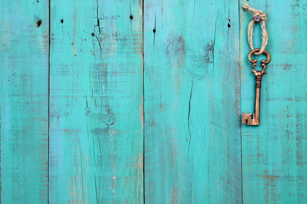 A key, on a piece of twine, hanging from a wooden wall, painted blue