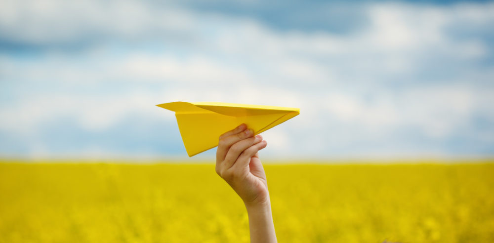 Paper airplane in children hands on yellow background and blue sky in cloudy day