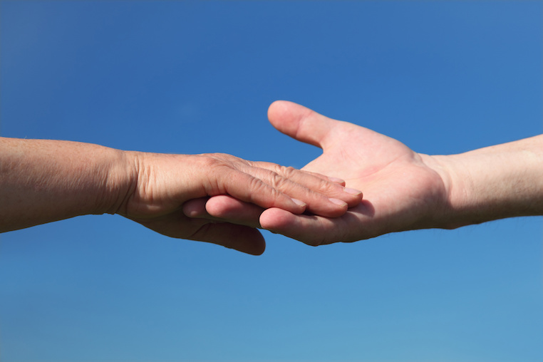 Two people, holding hands, with a blue sky behind